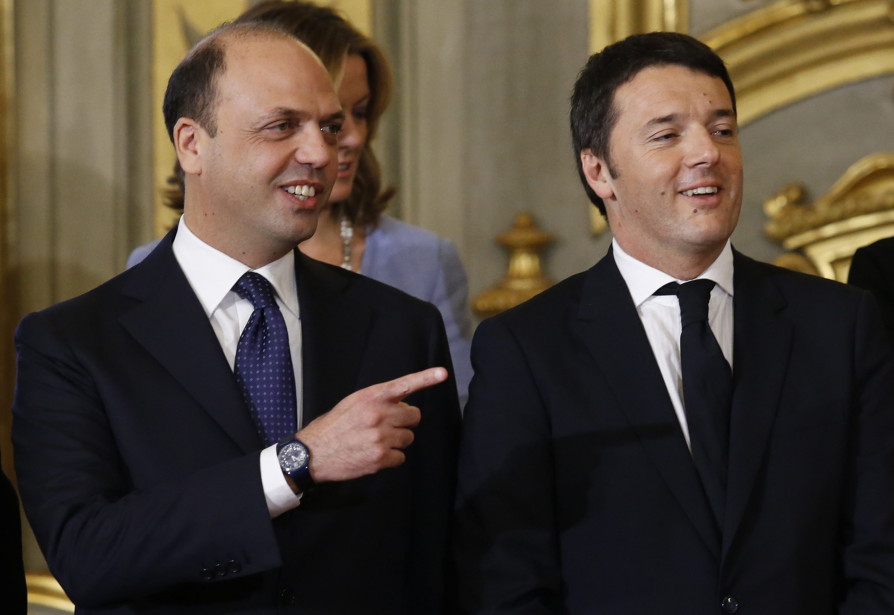 Newly appointed Italian Prime Minister Matteo Renzi (R) and Interior Minister Angelino Alfano talk during a swearing-in ceremony at Quirinale Palace in Rome February 22, 2014. Italian center-left leader Renzi promised on Friday to start work on reforms immediately, after he named a new cabinet and formally accepted the mandate to form an administration he said would stay in place until 2018. REUTERS/Remo Casilli  (ITALY - Tags: POLITICS)